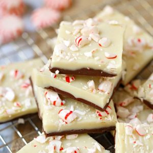 A Christmas favorite, this layered white chocolate peppermint fudge is perfect for holiday parties and gifting! Enjoy the layers of chocolate and white chocolate topped with crushed candy canes.