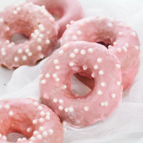 strawberry iced donuts stacked with white sprinkles